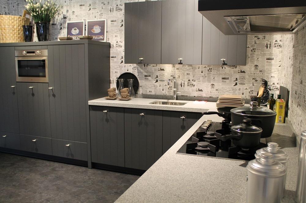 showroom keuken kuys keukens grijs, klassieke uitstraling met moderne elementen. licht gekleurd aanrechtblad, krantenpapier muur, keukenrenovatie
